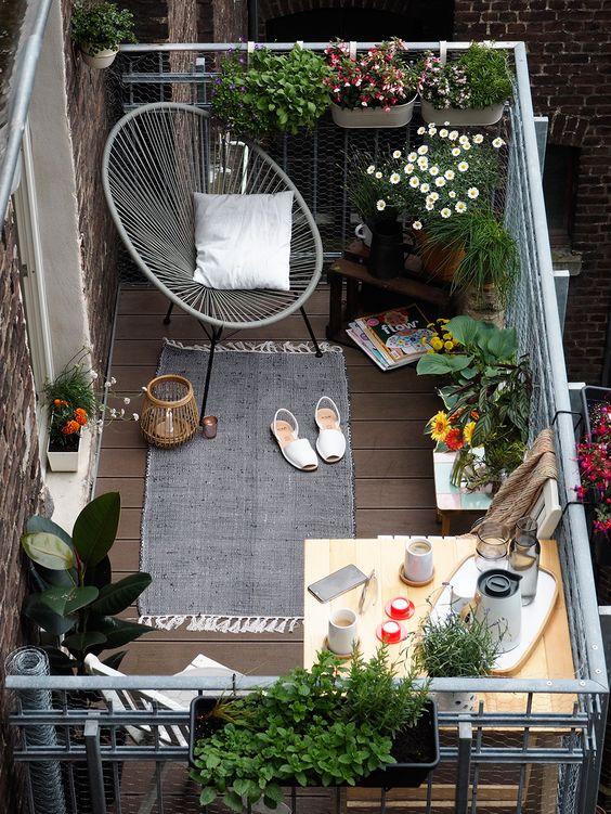 varanda de apartamento pequena decorada com vasinhos de flores, livros, uma poltrona moderna e um cantinho com mesinha rustica de café