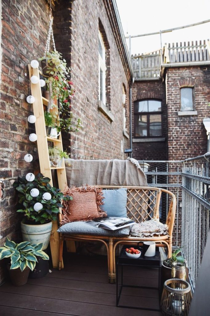 varanda com parede de tijolinhos decorada com uma escada com luminárias e flores