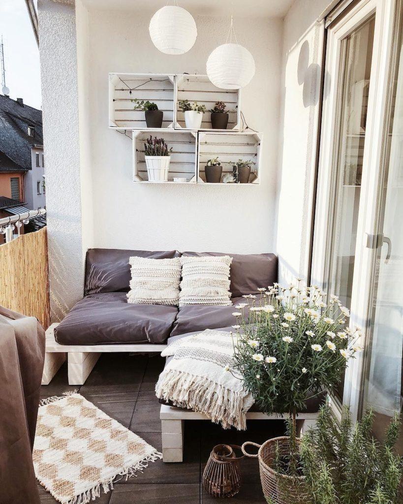 varanda pequena com paredes brancas decorada com caixotes pintados de branco e vasinhos de flor na cor marrom, combinando com um sofá de paletes pintados de branco e almofadas marrom
