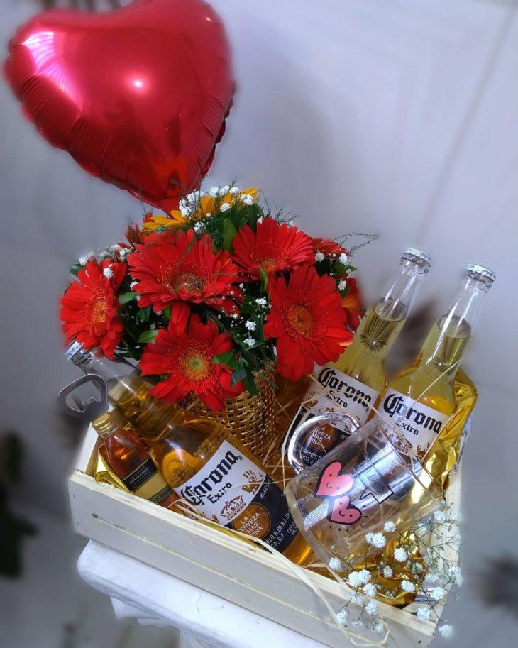 cesta para o dia dos namorados enfeitada com balão em forma de coração, flores vermelhas e 4 bebidas alcoólicas