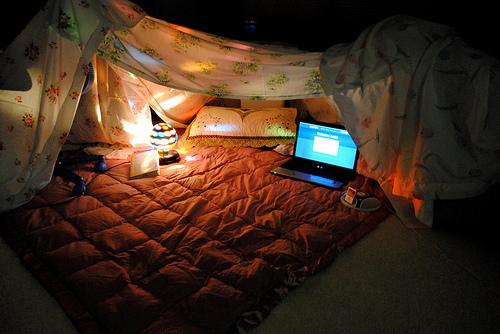 sala preparada para um cinema em casa na noite dos namorados com cobertor no chão, lençóis em forma de barraca com globo de luz e notebook para o filme