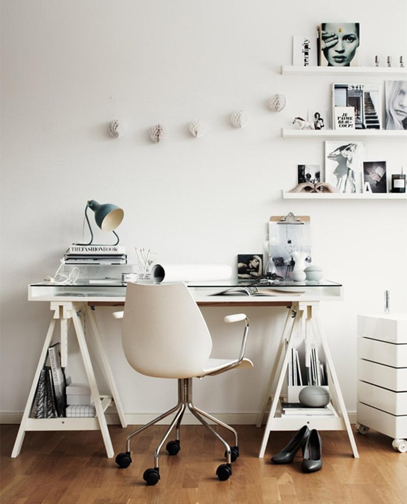 Mesa apoiada em cavaletes de madeira pintados de branco combinando com a cadeira de escritorio